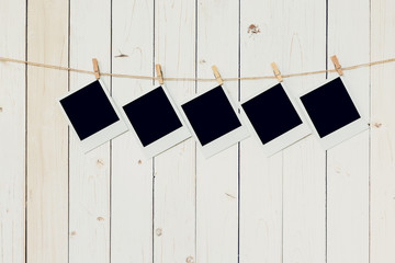 Five (5)blank photo frame hanging on white wood background with