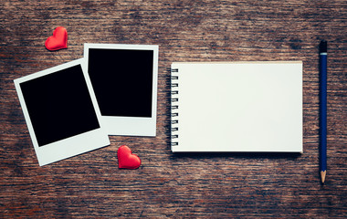 Blank photo frame, notebook, pencil and red heart for valentine