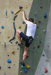 Mann klettert Wand hoch