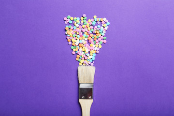 Colorful sprinkles with paintbrush on the purple background