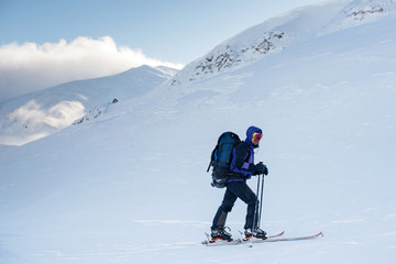 Hiker with a backpack goes to the winter mountains to ski tour i