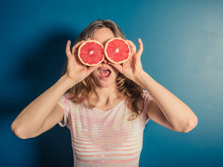 Young woman with grapefruit binoculars