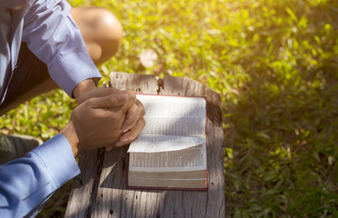 Young boy hands on bible. he is reading and praying bible on wooden table