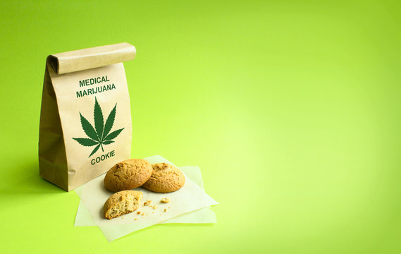 Cookies of medical marijuana in the kraft bag. Green background.