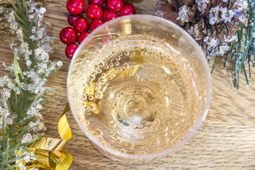 Closeup of bubbly drink from above on wood with berries, greener