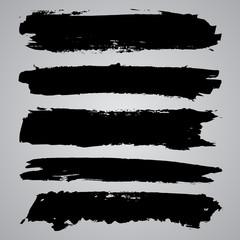 Set of black grunge brushstrokes on grey background. Abstract ha