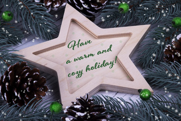 Christmas Xmas New Year Holiday greeting card with wooden five pointed star fir branches cones green berries and text Have a warm and cozy holidays