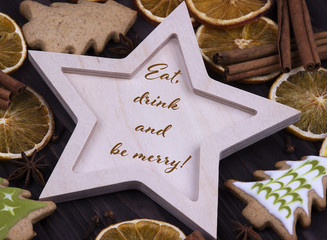 Christmas Xmas New Year Holiday greeting card with wooden star cinnamone star anice dried oranges Christmas tree cookies and text Eat drink and be merry