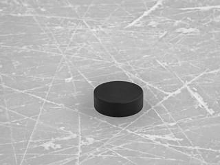 Hockey puck on ice hockey rink background