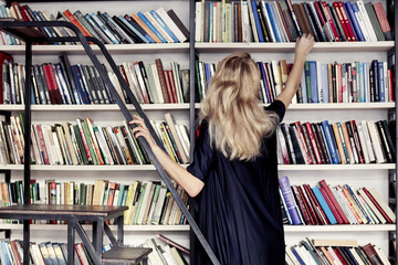Woman in a library take a book from bookshelf