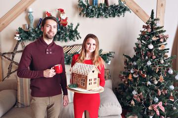 Husband and wife hold gingerbread house  embrace near christmas tree