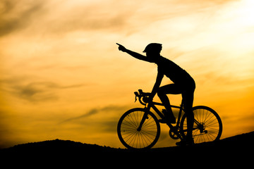 Silhouette of man with bicycle at sunset