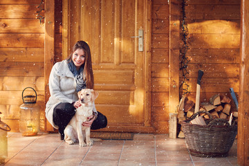 Girl with dog in front of wooden house