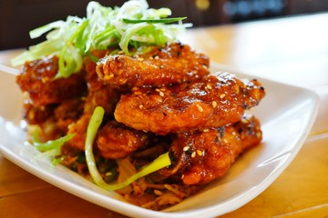 Platter of Korean barbecue chicken wings with scallions