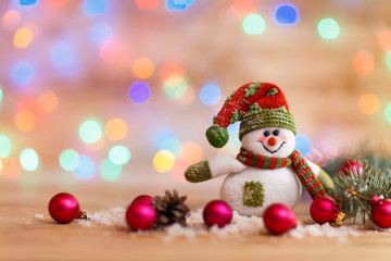 cheerful snowman in knit hat and Christmas decorations