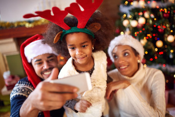 Happy family taking selfie during Christmas.