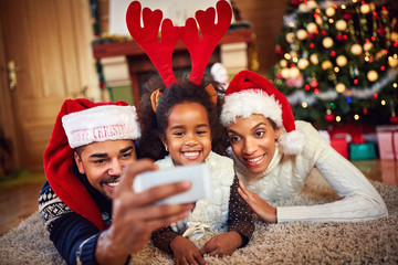 Black family taking Christmas selfie together