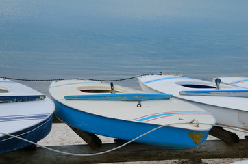 Traditional small hollow body board-style sailing dinghy sailboats on wooden racks by the water on the shoreline