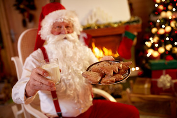 Santa Claus enjoying in traditional Christmas snack