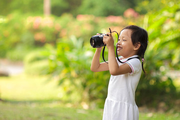 Beautiful child girl taking pictures at the nature field.