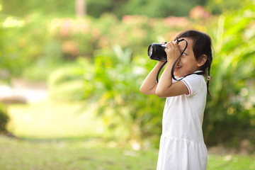 asian child girl taking pictures at the nature field.