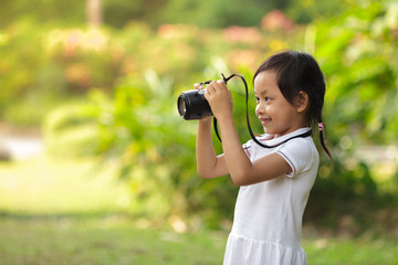 Beautiful child taking pictures at the nature field.