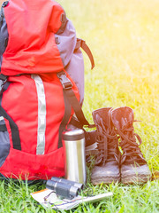 Hiking travel gear on glasses. Items include hiking boots, cup, map,binoculars. Flat lay of outdoor travel equipment items for mountain camping trip.