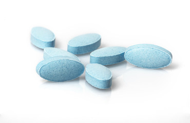 Small blue tablets spilling out of prescription container