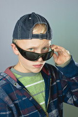 Young Blond Boy With Sunglasses And Cap Looking Cool