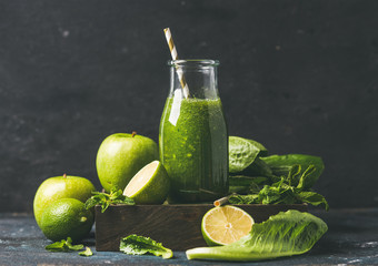 Green smoothie in glass bottle with apple, romaine lettuce, lime and mint, dark background, selective focus. Detox, dieting, clean eating, vegetarian, vegan, fitness or healthy lifestyle concept
