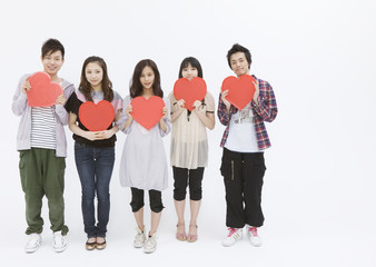 Young men and women holding heart shaped objects