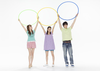 Young man and women holding hula hoops
