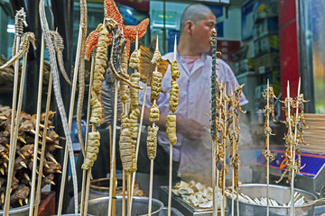 Scorpions, seahorses, starfish and other delicacies on skewers for sale at Wangfujing Street night market, Beijing, China, Asia