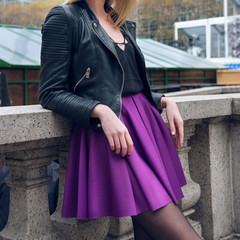 Female scater skirt and leather jacket. Girl wearing sexy fashionable outfit with black leather jacket and purple circle skirt. Model girl in fashion skirt..