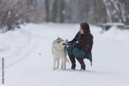 Happy caucasian brunette girl with husky dog outside in winter snowy forest outside stock - Keeping outdoor dog happy winter ...