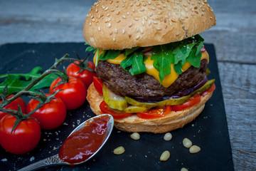 Homemade beef burger on a black slate background.