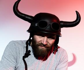 silhouette Rocker man in a horned helmet posing on red background