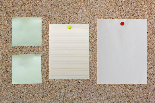 blank paper on corkboard with red and yellow pin