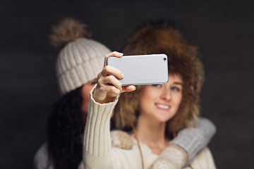 Two women doing selfie with smartphone.
