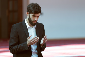 Younger Muslim man praying in colorful mosque