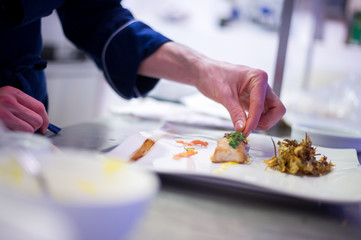 Chef preparing a cod filet with artichokes