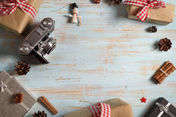 Vintage photo camera on christmas wooden background with gift boxes. top view with copy space