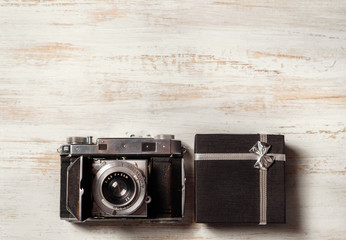 Vintage photo camera on wooden background with gift box. top view. copy space