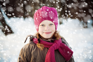 Young Girl in Pink Hat and Scarf in Park in Snowy Winter Day. Ch
