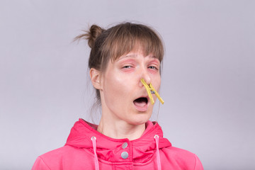 Fed up with Sneezing Woman Blocks her Nose with a Clothing Peg