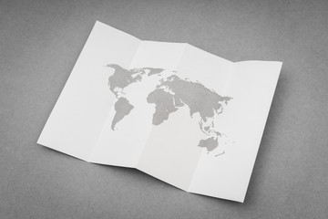 Paper folded with world map .
