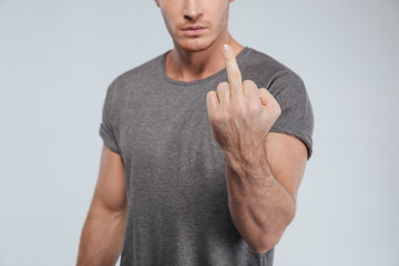 Cropped image of a young serious man showing fuck sign