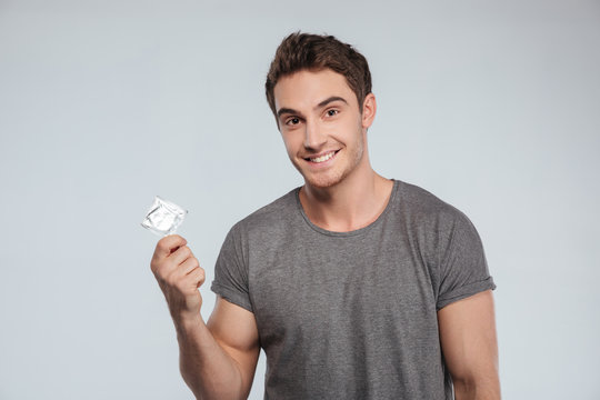Portrait of a smiling casual man holding condom