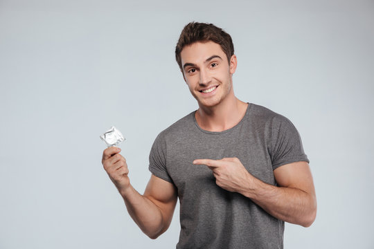 Portrait of a young smiling man pointing finger at condom