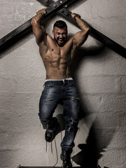 Muscular Man Holding on the Wall